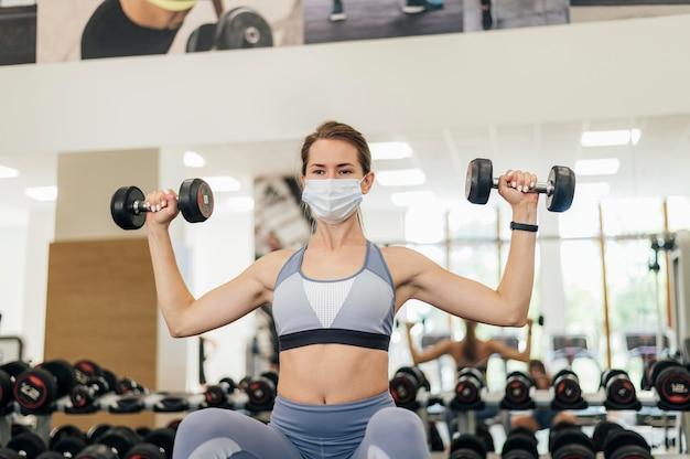 유행병 동안 체육관에서 운동하는 의료 마스크를 가진 여자