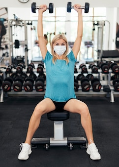 Woman with medical mask exercising during the pandemic at the gym