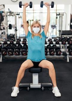 체육관에서 유행병 동안 운동 의료 마스크를 가진 여자