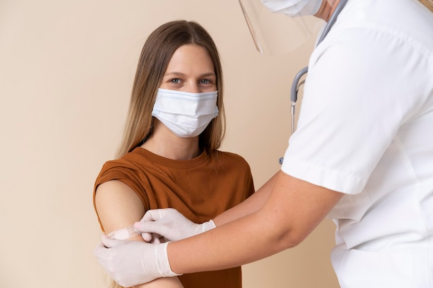 Woman with medical mask getting sticker on arm after getting a vaccine