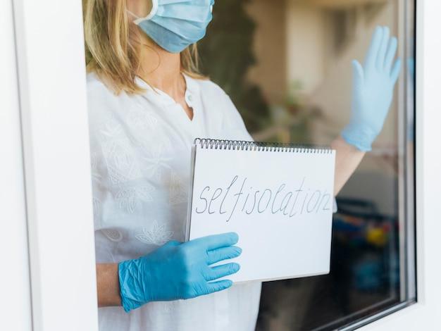Donna con maschera medica e guanti che tengono taccuino domestico di soggiorno