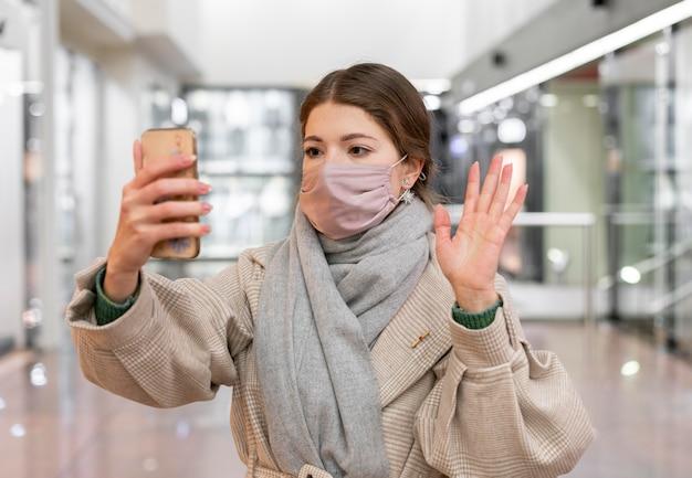 영상 통화를 갖는 의료 마스크를 가진 여자