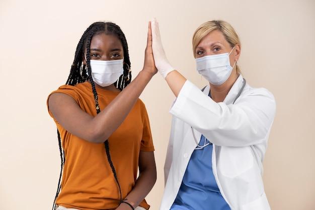 백신 접종 후 의사 하이 파이브 의료 마스크를 가진 여자