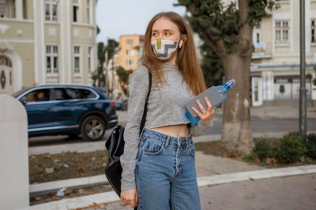 Donna con mascherina medica che tiene una bottiglia d'acqua