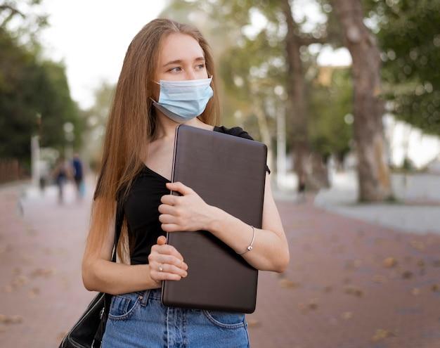 Donna con mascherina medica che tiene un computer portatile all'esterno
