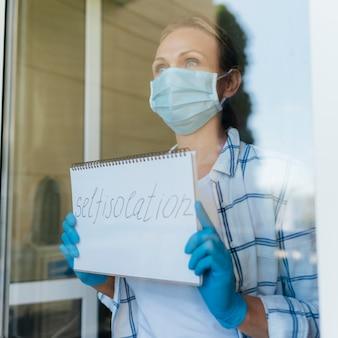 Donna con la mascherina medica che tiene il taccuino domestico di soggiorno alla finestra