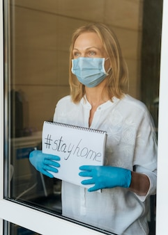 Woman with medical mask holding stay home notebook at the window