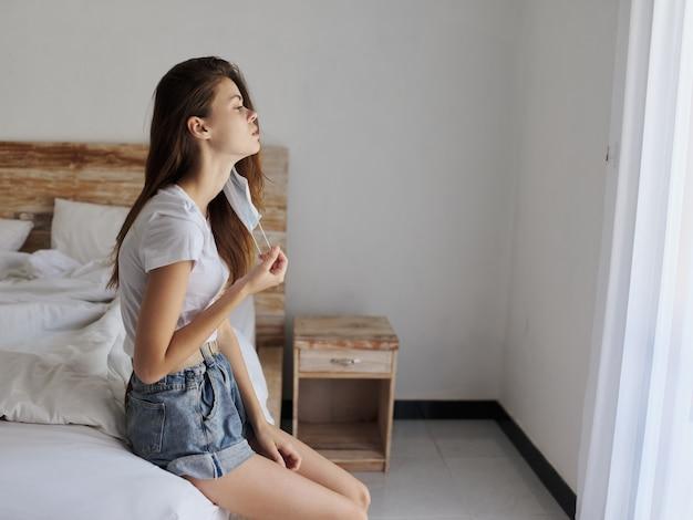 手に医療マスクを持つ女性は、屋内の側面図のベッドに座っています