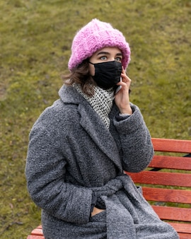 도시에서 의료 마스크를 가진 여자는 벤치에서 전화로 대화