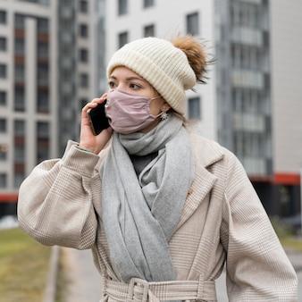 전화로 대화하는 도시에서 의료 마스크를 가진 여자