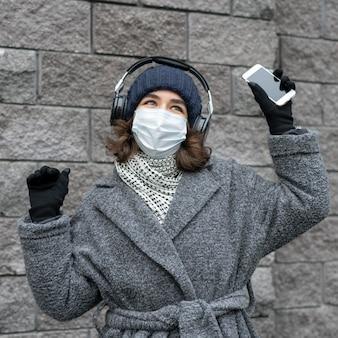 Женщина с медицинской маской в городе слушает музыку в наушниках и смартфоне
