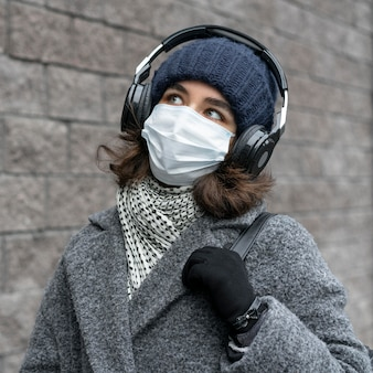 音楽を聴いている街で医療マスクを持つ女性