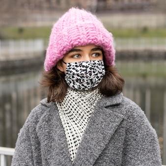 都市公園で医療マスクを持つ女性