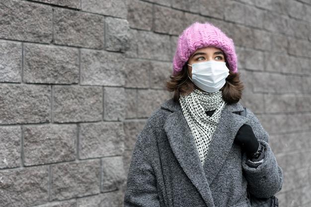 コピースペースのある街で医療マスクを持つ女性