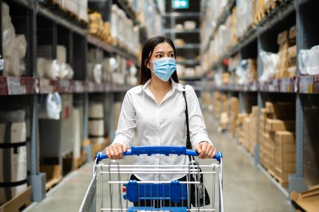 コロナウイルスのパンデミック中に倉庫店で探して買い物をしている医療マスクを持つ女性