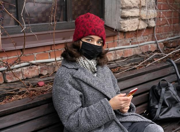 스마트 폰을 사용하여 벤치에 야외 의료 마스크를 가진 여자