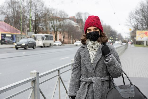 Женщина с медицинской маской на открытом воздухе гуляет