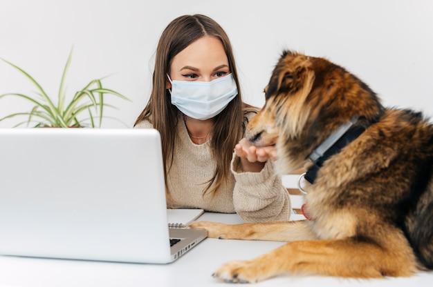 Женщина с медицинской маской играет со своей собакой