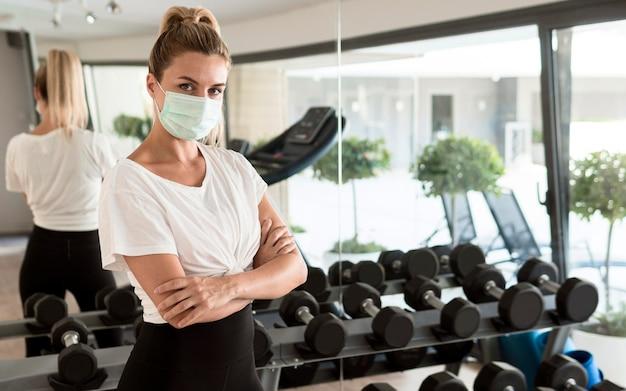 Женщина с медицинской маской позирует в тренажерном зале