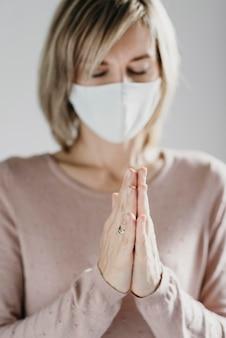 Donna con mascherina medica che prega a casa