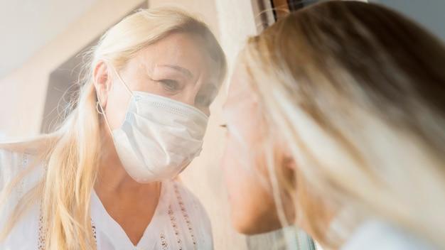 Donna con mascherina medica in quarantena dietro la finestra con bambino