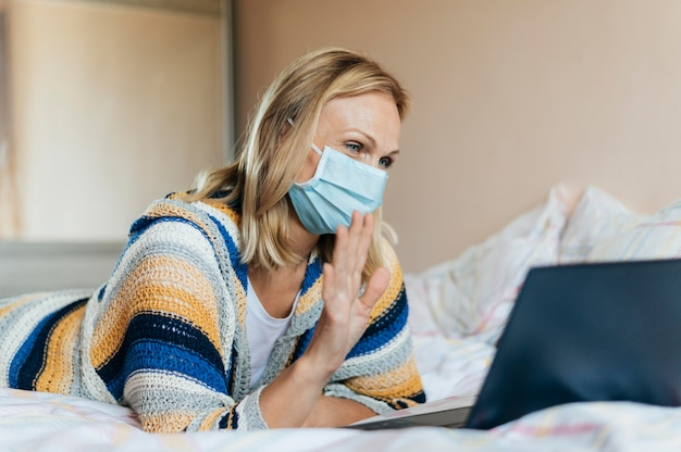 Woman with medical mask in quarantine with laptop