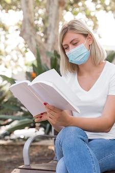 ベンチに座って本を読んで医療マスクを持つ女性
