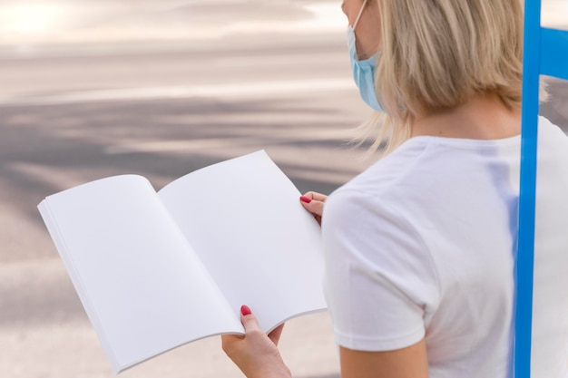 屋外で本を読んで医療マスクを持つ女性
