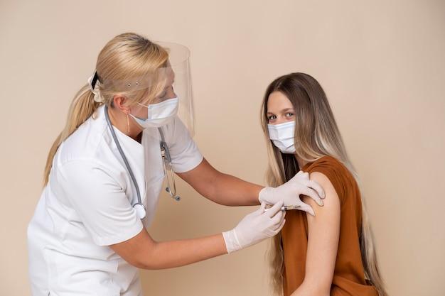 Женщина с медицинской маской получает вакцину