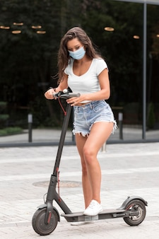 Woman with medical mask riding electric scooter
