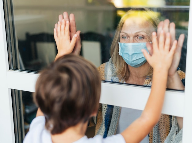 Женщина в медицинской маске здоровается с племянником через окно