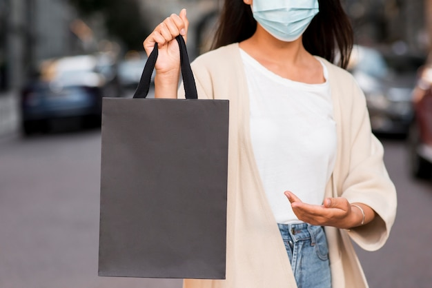 Woman with medical mask showing off shopping bag that she's holding