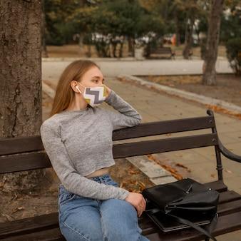 Donna con mascherina medica seduta su una panchina