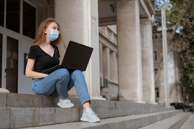 Женщина с медицинской маской сидит на лестнице снаружи с копией пространства