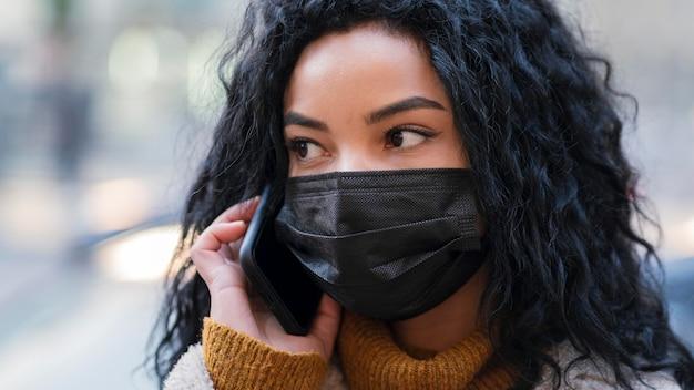 電話で話している医療マスクを持つ女性
