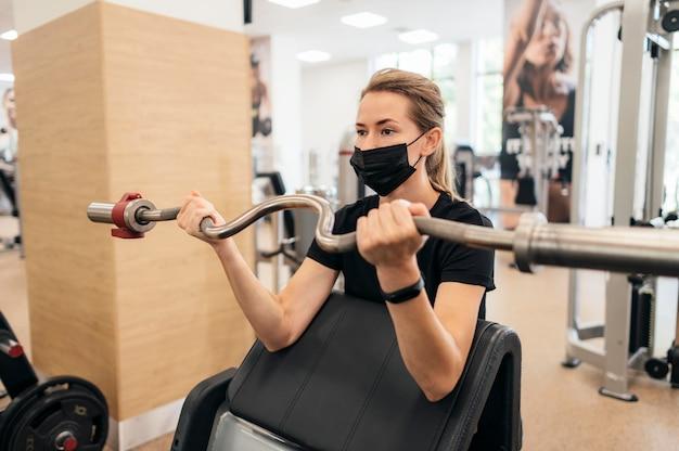 ジムで医療マスクのトレーニングを受けている女性