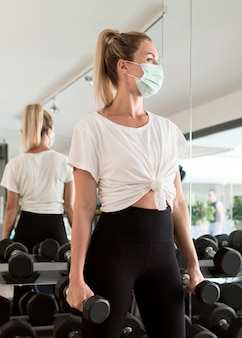 Женщина с медицинской маской тренируется в тренажерном зале