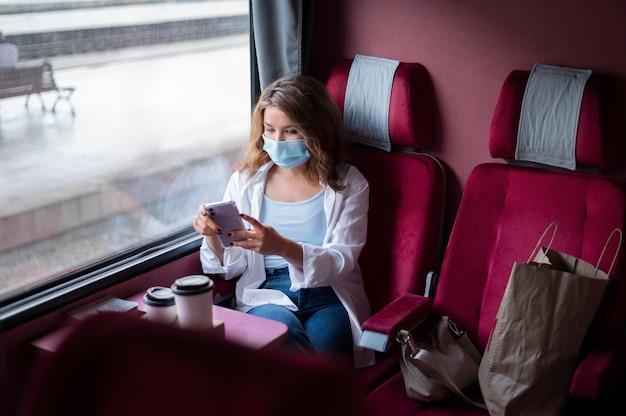 Женщина с медицинской маской путешествует на общественном поезде и использует смартфон