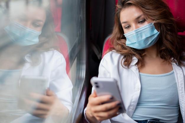 공공 기차로 여행하고 스마트폰을 사용하는 의료 마스크를 쓴 여성