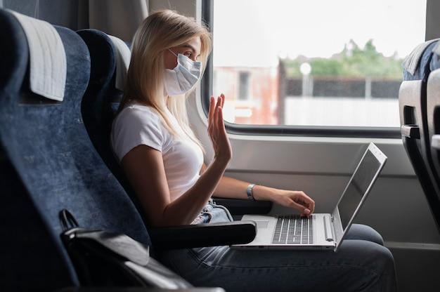 Donna con maschera medica che viaggia in treno pubblico e fa una videochiamata sul laptop