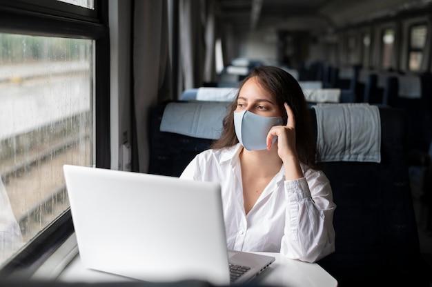Donna con maschera medica che viaggia in treno pubblico e usa il laptop