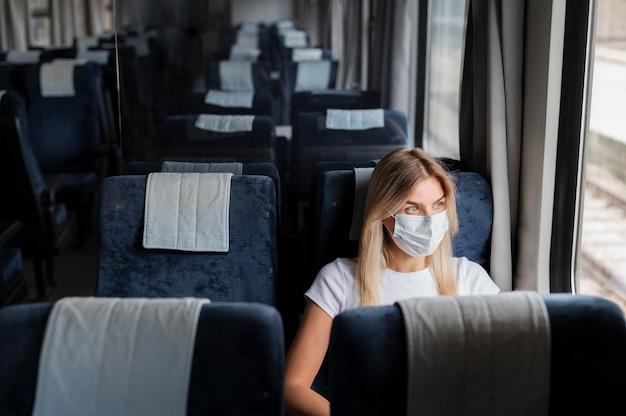 공공 기차로 여행하는 의료 마스크를 쓴 여성