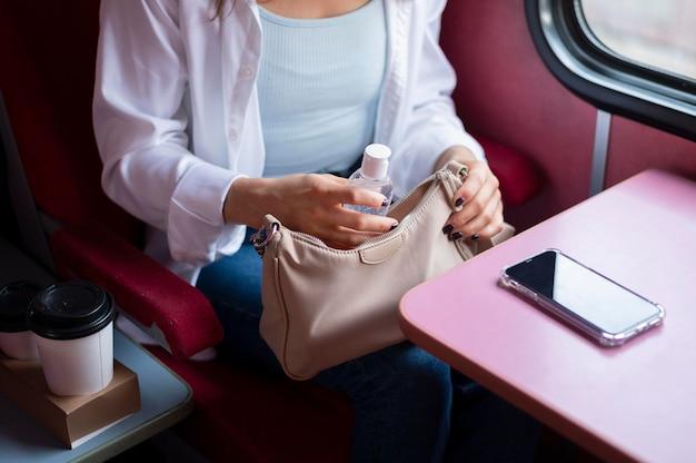Женщина с медицинской маской использует дезинфицирующее средство для рук во время поездки на общественном поезде