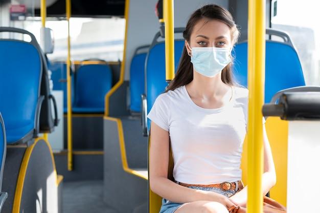 Donna con maschera medica che utilizza autobus pubblico per il trasporto