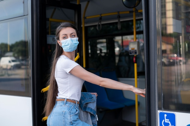 Woman with medical mask using public bus for transportation