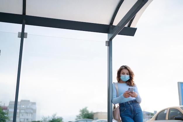 공공 버스 정류장에서 스마트폰으로 의료 마스크를 쓴 여성