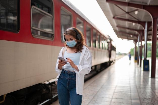 Женщина с медицинской маской с помощью смартфона на общественном вокзале