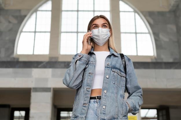 公共の駅でスマートフォンを使用して医療マスクを持つ女性
