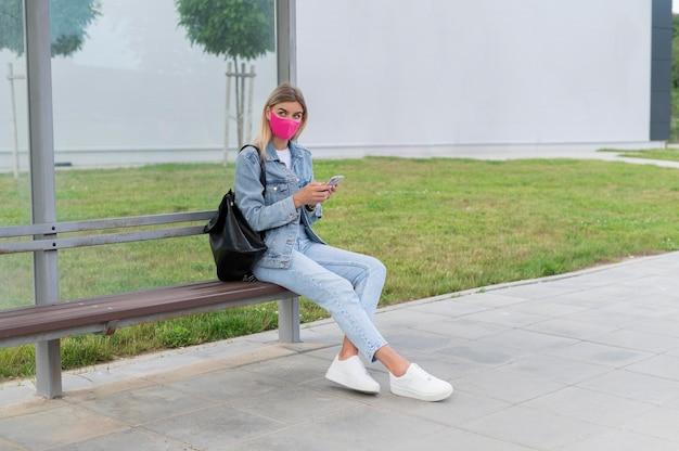 Donna con maschera medica che utilizza smartphone mentre aspetta l'autobus pubblico