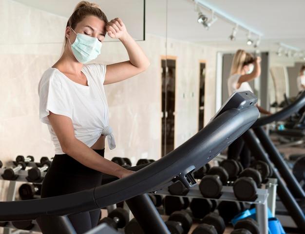 Женщина с медицинской маской работает в тренажерном зале